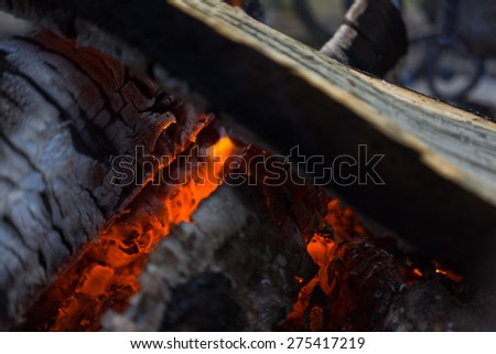 Burning smolder firewood in the fireplace close up - stock photo