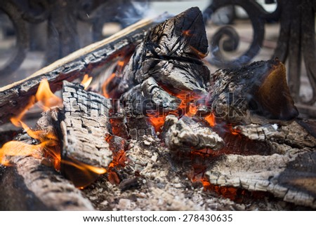 Burning smoldering firewood in the fireplace close up. Firewood. Coals. Extinguished the fire. The ashes. - stock photo