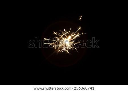 burning sparkler on a dark background - stock photo