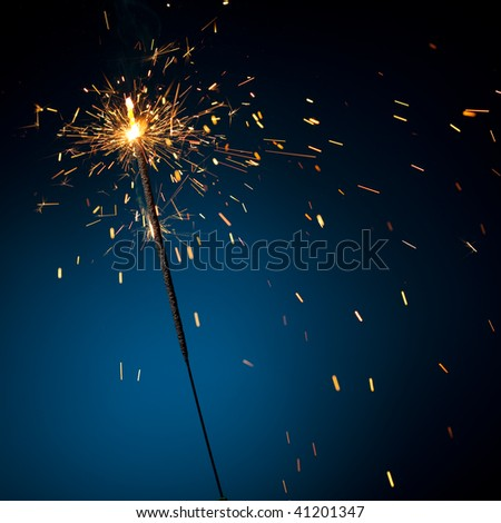 burning sparkler on blue - stock photo