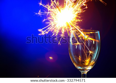 burning sparklers in a Cup on wooden table on blue background - stock photo