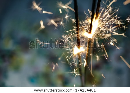 Burning Sparklers with colorful Confetti on wooden Table at a Party - stock photo