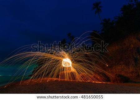 Burning steel wool on the top rock behind beach in twilight time.