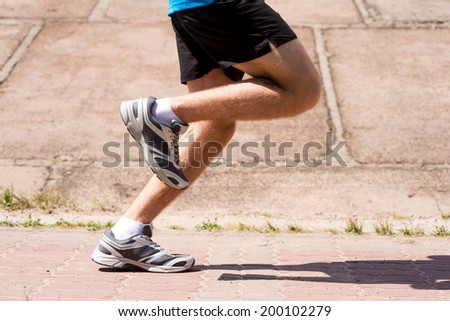Burning the miles away.  Side view close-up image of man running outdoors  - stock photo
