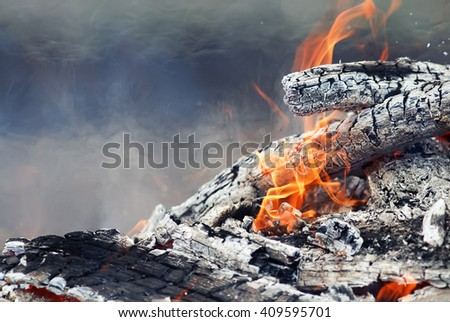 burning up white hot coals and the bright red flames of a fire - stock photo