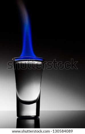 Burning vodka in shot on a black background - stock photo