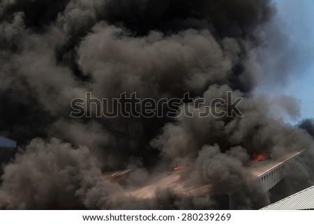 Burning warehouses with black smoke - stock photo