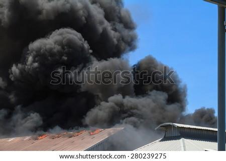 Burning warehouses with black smoke against blue sky - stock photo