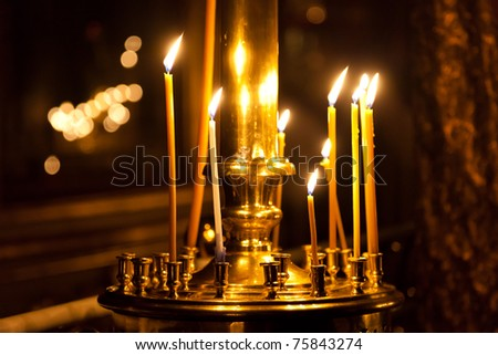 Burning wax candle flame light in religion church - stock photo