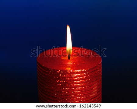 burning wax candle on a blue background - stock photo