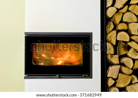 burning wood in fireplace insert. Wood stand with wood