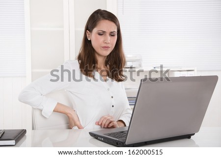 Burnout : tired businesswoman frowning at laptop
