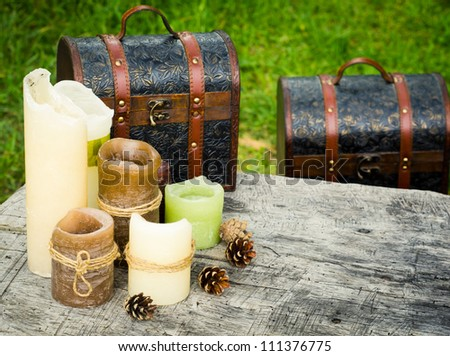 Burnt candles and shabby chests on an old wooden table - stock photo