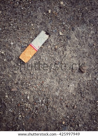 Burnt cigarette stub butt on dirty sand ground floor, vintage effect