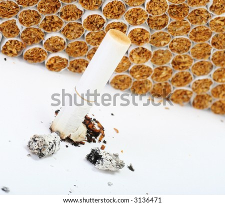 burnt cigarette with stack of new product in the back, easily converts to sepia or black an white - stock photo