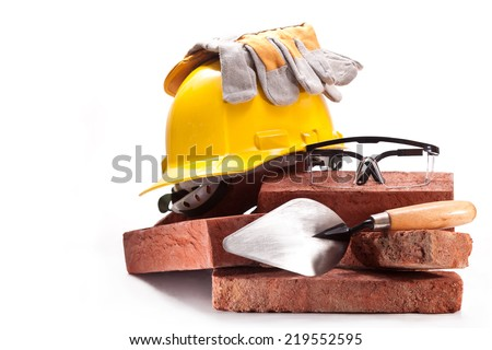 Burnt clay bricks, yellow helmet with gloves, trowel and goggles - stock photo