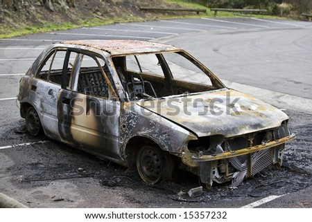 Burnt out car dumped by the side of the road. - stock photo