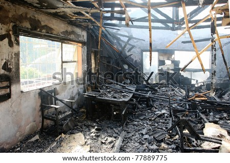 Burnt out house with charred roof trusses and burnt furniture - stock photo