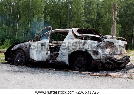 Burnt out rusted old car near the road and forest - stock photo