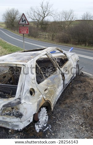 Burnt out shell of car on country road