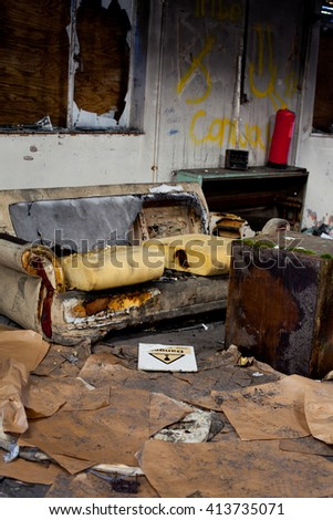 Burnt out sofa in a derelict building with lots of rubbish and a danger sign on the floor