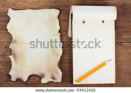 Burnt Paper, Notepad (antique 1943 year) and Pencil on wood background - stock photo
