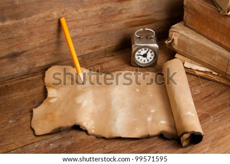 Burnt paper, pencil, vintage clock and old books on wood - stock photo
