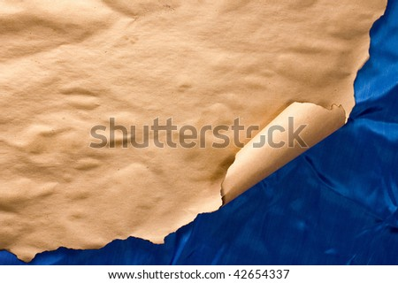 Burnt parchment rolled at corner on wrinkled blue textile - stock photo