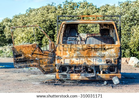Burnt truck surrounded by nature - stock photo