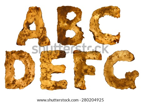 Burnt vintage decrepit dark ocher burned cardboard alphabet with black spots isolated on white background with clipping path - stock photo