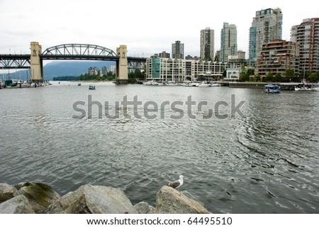 Burrard bridge and surrounding condo buildings and water in Vancouver, British Columbia Canada - stock photo
