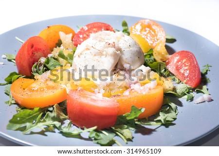 Burrata mozzarella on a colored tomato salad and roquette - stock photo
