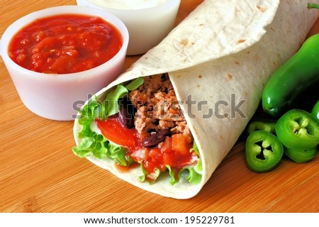 Burrito filled with meat and vegetables with salsa and peppers on wood