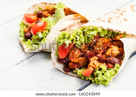 Burrito. Tortilla with meat and beans on a table - stock photo