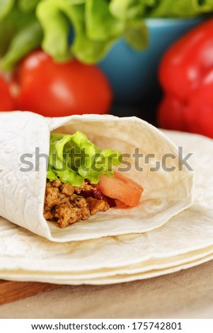 burrito with beef tomato and salad leaf on old wooden table rustic style