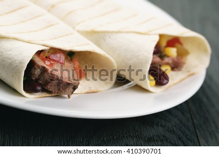 burritos with beef steak, corn, black beans and salsa sauce on wood table