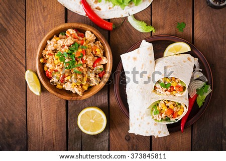 Burritos wraps with chicken meat, corn, tomatoes and peppers on wooden background. Top view - stock photo
