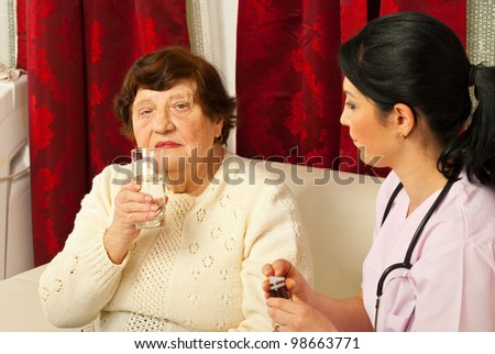 Burse giving treatment and glass with water to senior woman in her home - stock photo