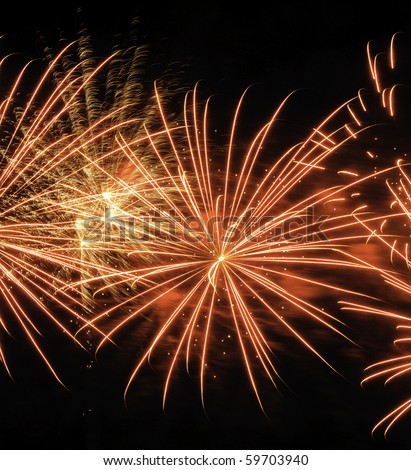 Bursts of yellowish fireworks near puffs of reddish smoke and motion-blurred streaks from previous explosion - stock photo
