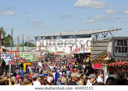 BURTON, OH - SEPT 5: Crowds throng the midway at the 188th annual Great Geauga County Fair, the state's oldest continuously running fair on September 5, 2010 in Burton, Ohio. - stock photo