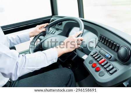 Bus driver in cockpit at the wheel driving - stock photo