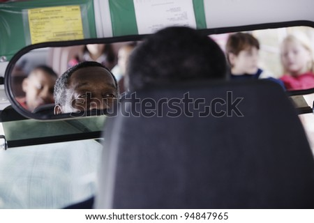 Bus driver looking at children in rear view mirror - stock photo