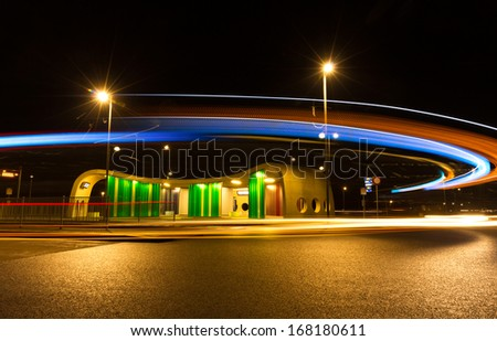 Bus driving by a colorful bus stop at night. Long exposure. - stock photo