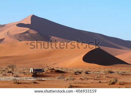 Bus full with tourist driving towards the red dunes of Sossusvlei, Namib Naukluft National Park, Namib desert, Namibia.