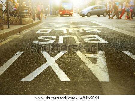 Bus in bus lane out of focus, traffic. Bus and taxi sign painted on street in focus. - stock photo