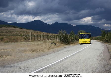 Bus on old mountain road in dramatic cloudy weather.
