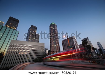Bus speeding in downtown Los Angeles at twilight. - stock photo