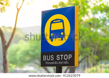 Bus stop sign on post pole next to the road. Traffic road sign. Blue signage signpost. - stock photo