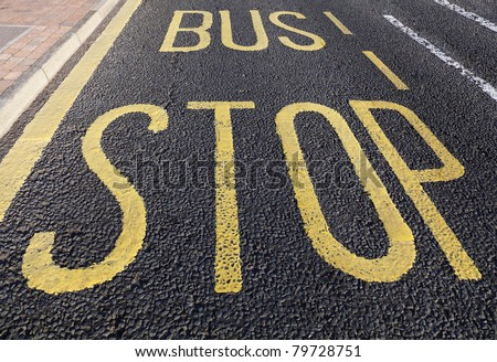 Bus stop sign painted on asphalt road - stock photo