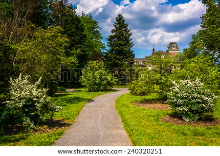 Bushes and trees along a path and the Cylburn Mansion at Cylburn Arboretum, Baltimore, Maryland. - stock photo